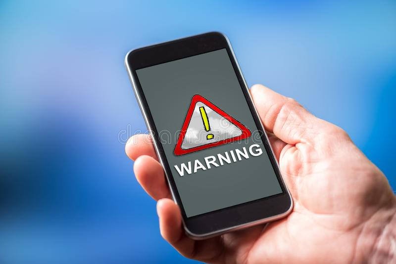 Warning concept on a smartphone. Smartphone screen displaying a warning concept royalty free stock images
