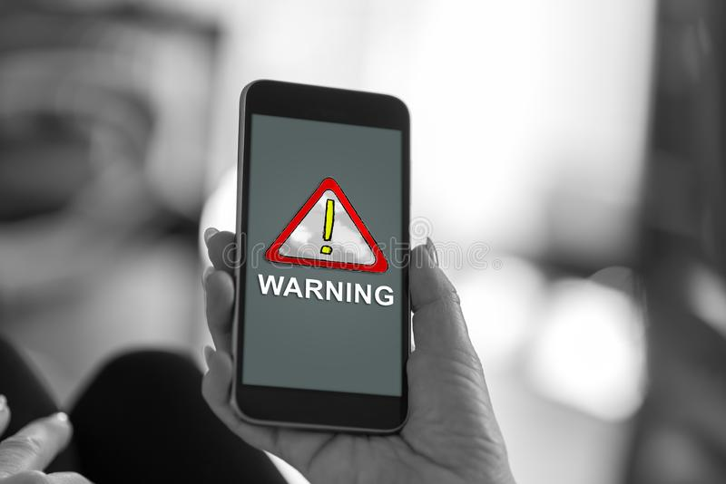 Warning concept on a smartphone. Smartphone screen displaying a warning concept royalty free stock photography
