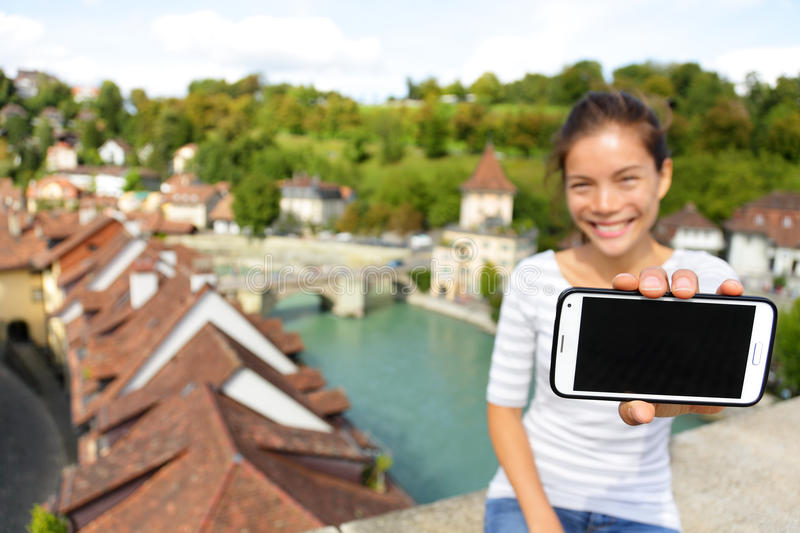 Smartphone screen - Woman showing app in Bern. Switzerland, Europe. Girl holding blank empty smart phone screen on travel with copy space. Happy smiling Asian stock photos