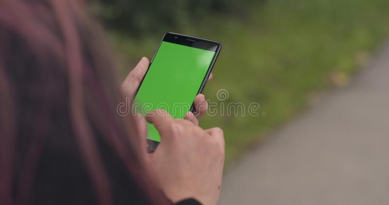 Smartphone se tenant de l'adolescence femelle avec l'écran vert sur le trottoir en ville image stock