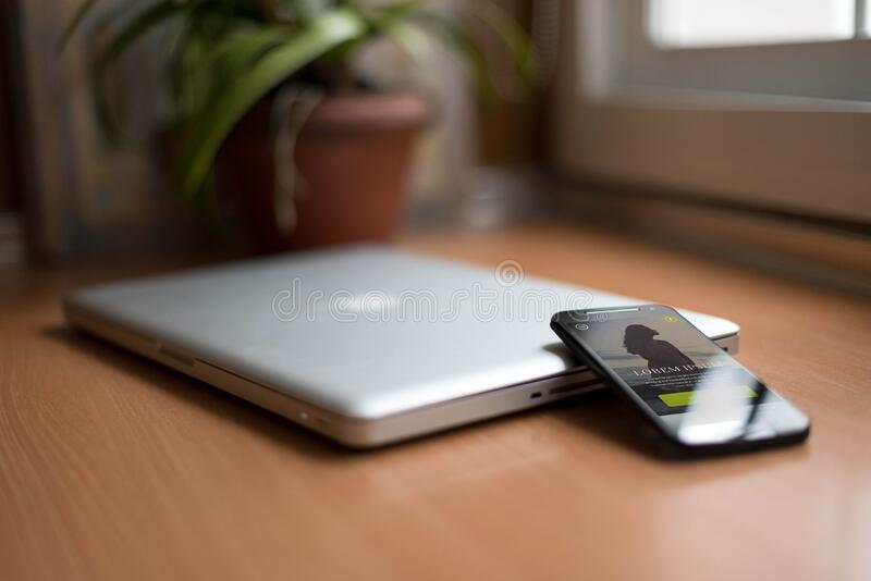 Smartphone Beside Silver Macbook on Brown Wooden Table With Potted Plant in the Background stock photos