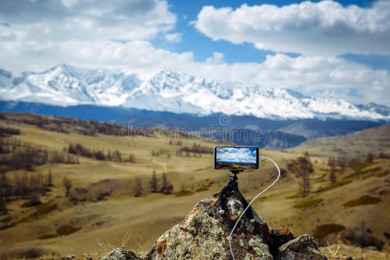 Smartphone on small tripod takes pictures of the mountain range and the clouds above the snowy peaks.  Blurred background, focus royalty free stock photos