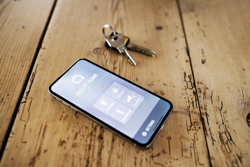 A smartphone with smart home screen and keys on wooden table. A smartphone with smart home control system. Keys on the old wooden table. Top view stock photos