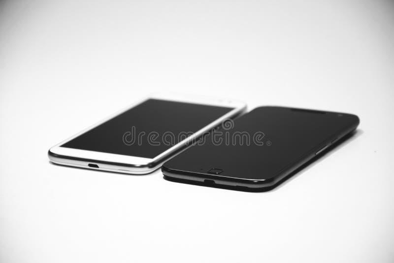 Άσπρο αρρενωπό Smartphone κοντά σε μαύρο αρρενωπό Smartphone στοκ εικόνες