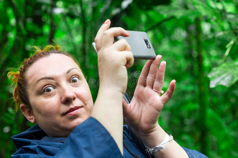 Smartphone Snapshot Photography. Funny Face Of Tourist Woman Into The Jungle While Snapping A Photo With Her Mobile Phone royalty free stock image