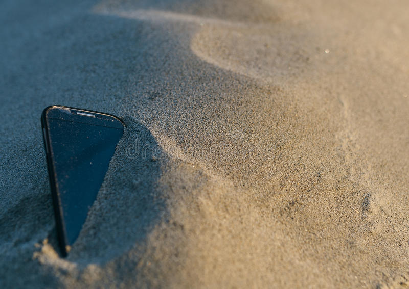 Smartphone som är borttappad i sanden royaltyfria foton