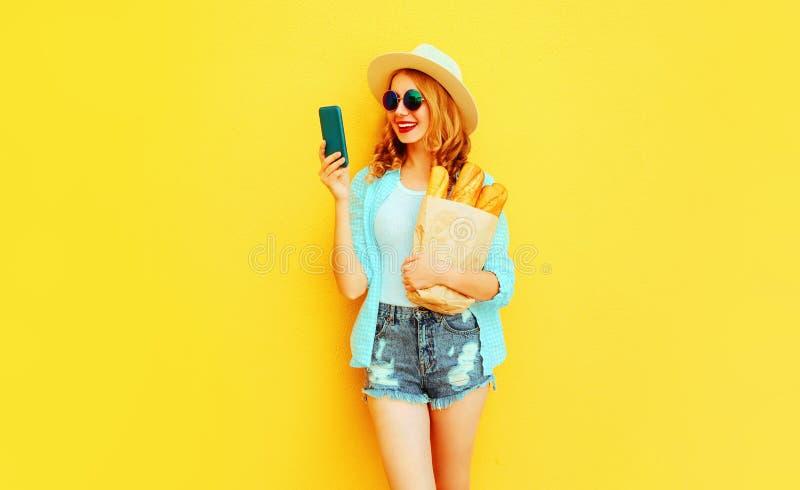 Smartphone sonriente feliz de la tenencia de la mujer del retrato, bolsa de papel con el baguette largo del pan blanco, sombrero  imágenes de archivo libres de regalías
