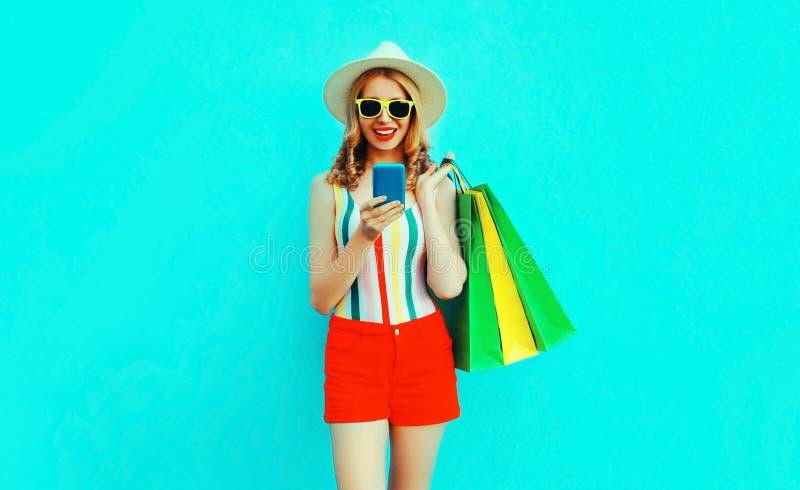 smartphone sonriente feliz de la tenencia de la mujer joven con los bolsos de compras en la camiseta colorida, sombrero de paja d imagenes de archivo
