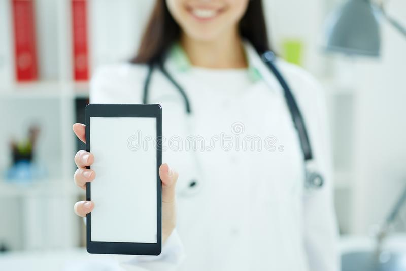 Smartphone with space for text or image in the hand of female doctor. Medical advertisment concept. Photo with depth of. Smartphone with space for text or image royalty free stock photos