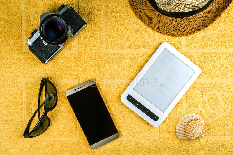 A smartphone, a straw hat, sun glasses, film camera, eBook and a shell stock photo