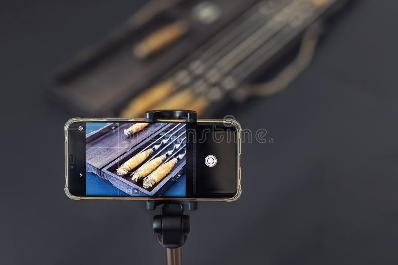 Smartphone sugli oggetti della fucilazione del treppiede allo studio dell'interno della foto Fotografia professionale dell'oggett immagine stock