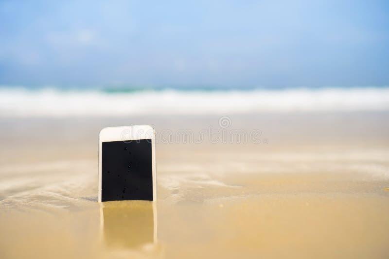 Smartphone sulla spiaggia tropicale di estate della sabbia il giorno di vacanza fotografie stock libere da diritti