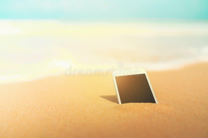 Smartphone sulla spiaggia tropicale di estate della sabbia il giorno di vacanza fotografia stock libera da diritti