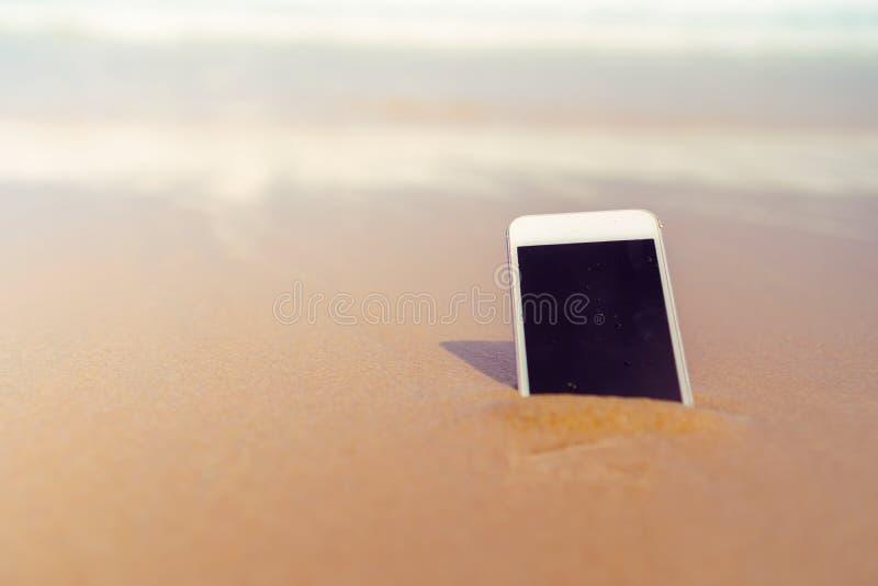 Smartphone sulla spiaggia tropicale di estate della sabbia il giorno di vacanza fotografie stock