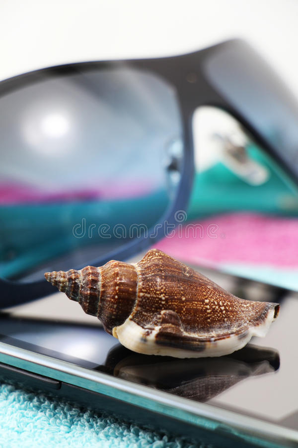 Smartphone and sunglasses, on a beach towel. A composition with a pair of fashion sunglasses and a seashell on a blue beach towel, detail, white background stock image