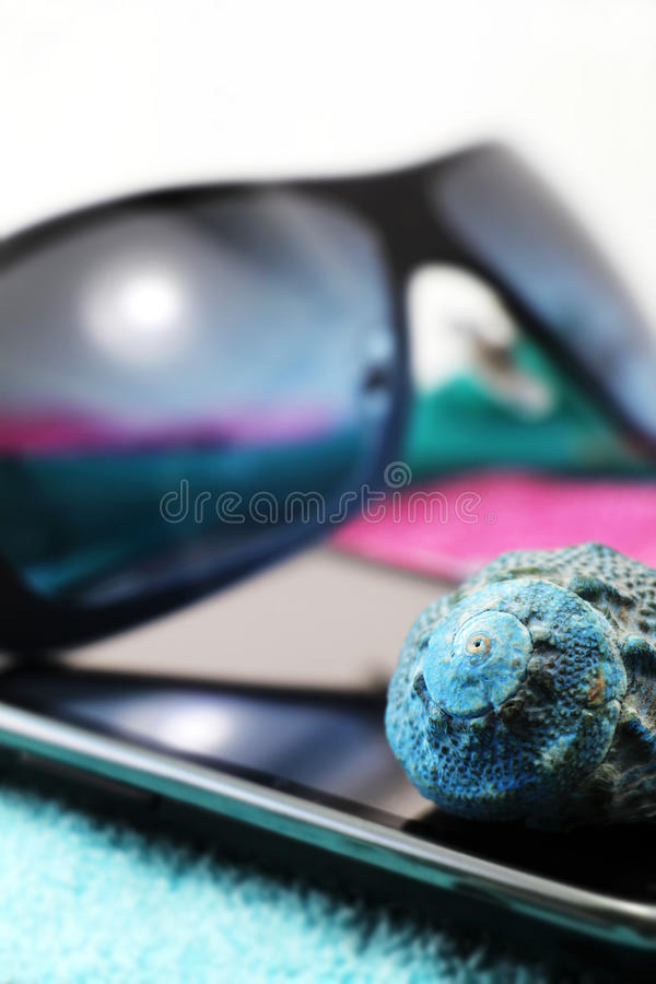 Smartphone and sunglasses, miniature style. A composition with a pair of fashion sunglasses and a smartphone on a blue beach towel, detail, white background stock photography