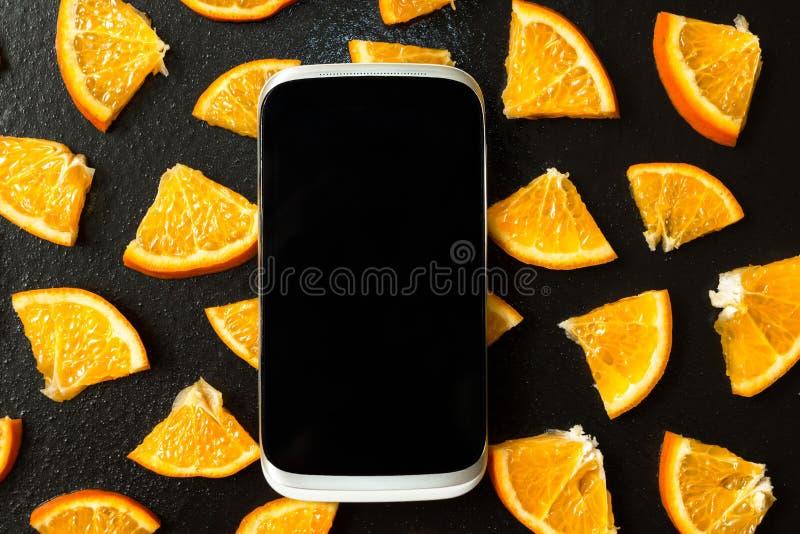 Smartphone sur le fond des tranches oranges photos stock