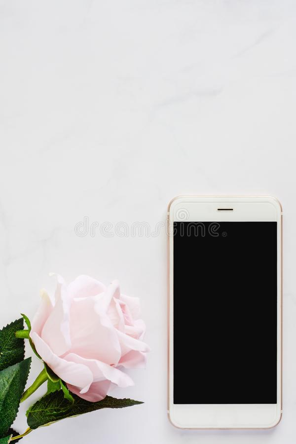 Smartphone with sweet pink rose on white marble background stock images
