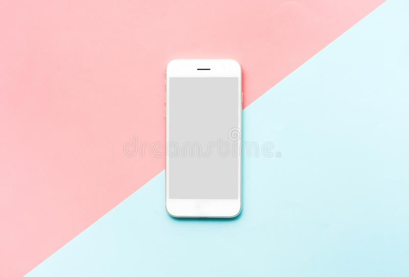 Smartphone, téléphone portable blanc sur le fond coloré Configuration plate photographie stock