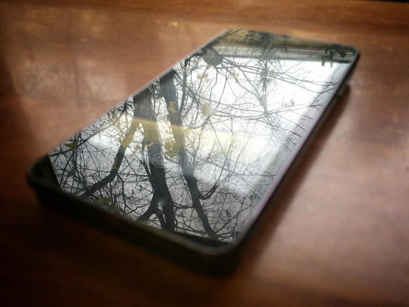 Smartphone is on the table. Reflection of a tree without leaves outside the window stock image