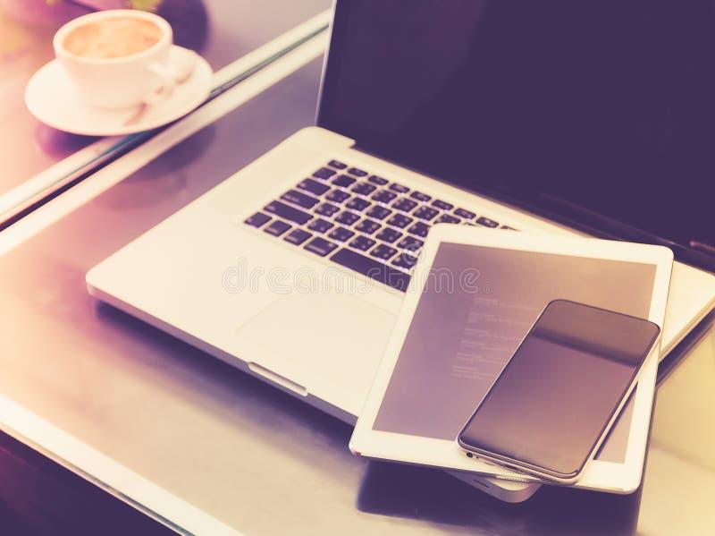 Smartphone, tablet en laptop op de lijst met de achtergrond van de koffiekop royalty-vrije stock foto