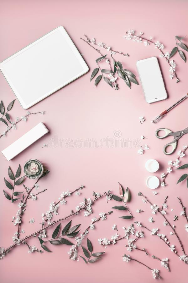Smartphone and tablet pc mock up on pastel pink desktop background with cosmetic, stationery supples and blossom branches, top royalty free stock image