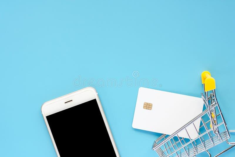 Smartphone, tarjeta de crédito blanca en blanco y mini carro de la compra o tr foto de archivo
