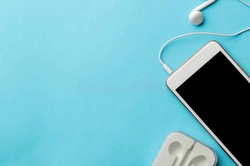 Smartphone Teléfono y auriculares blancos en un fondo azul claro brillante Visi?n superior Espacio para el texto fotos de archivo