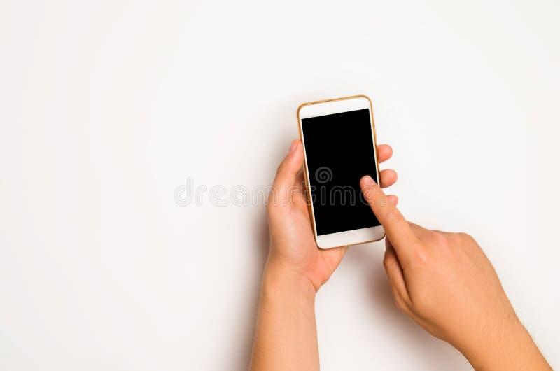 Smartphone, telefono in mani maschii su un fondo bianco Il concetto della comunicazione uso degli aggeggi, tecnologie moderne Soc fotografia stock