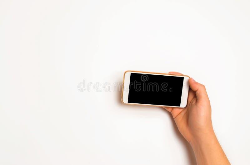 Smartphone, telefono in mani maschii su un fondo bianco Il concetto della comunicazione uso degli aggeggi, tecnologie moderne Soc immagine stock
