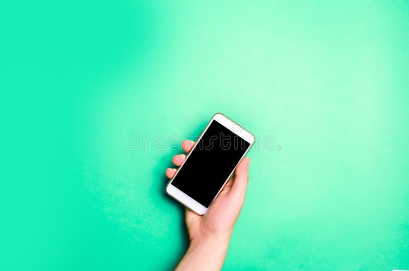 Smartphone, telefoon in mannelijke handen op een groene achtergrond Het concept mededeling gebruik van gadgets, moderne technolog stock foto