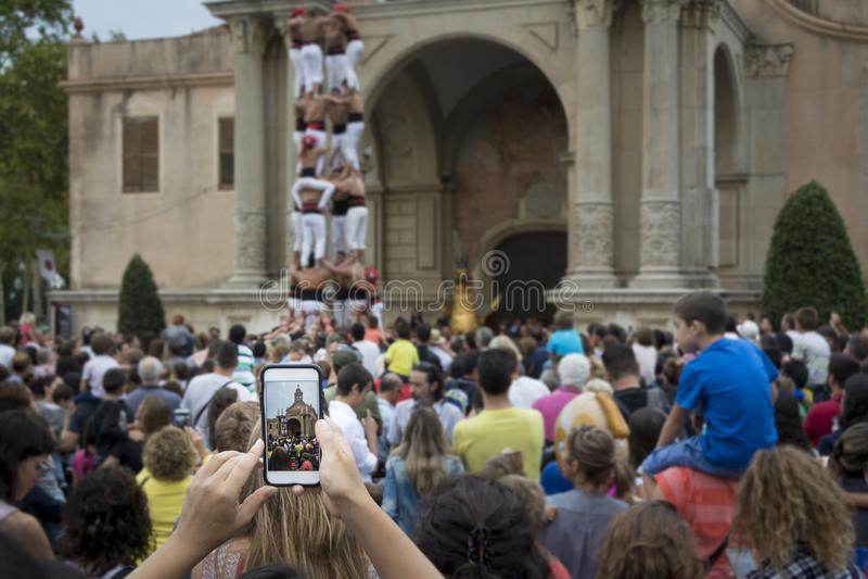 Smartphone tenuto in mano che prende un'immagine della prestazione di Castells fotografia stock