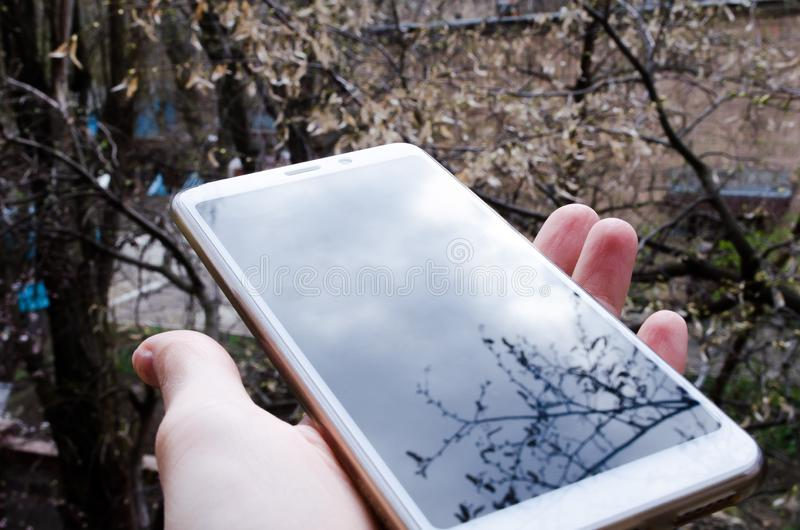 Smartphone ter beschikking Telefoneer ter beschikking Telefoon op de straat met lichte bezinning stock fotografie