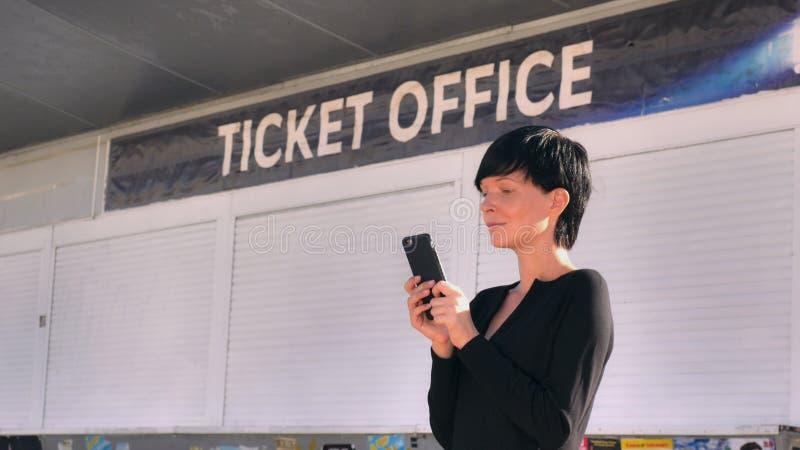 Smartphone texting fêmea do uso do ar livre imagens de stock