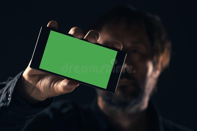 Smartphone ?tl?je upp i den manliga handen fotografering för bildbyråer