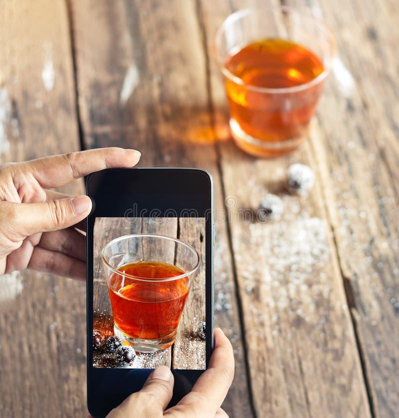 Smartphone toma las fotos del té y de la uva en el fondo de madera, concepto vibrante imagenes de archivo