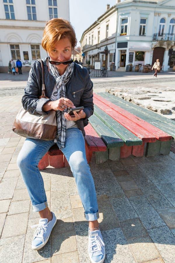 Smartphone turístico del uso de la mujer en la ciudad vieja de Kosice, Eslovaquia foto de archivo libre de regalías