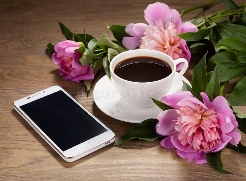 Smartphone, uma xícara de café e flores na tabela velha imagem de stock