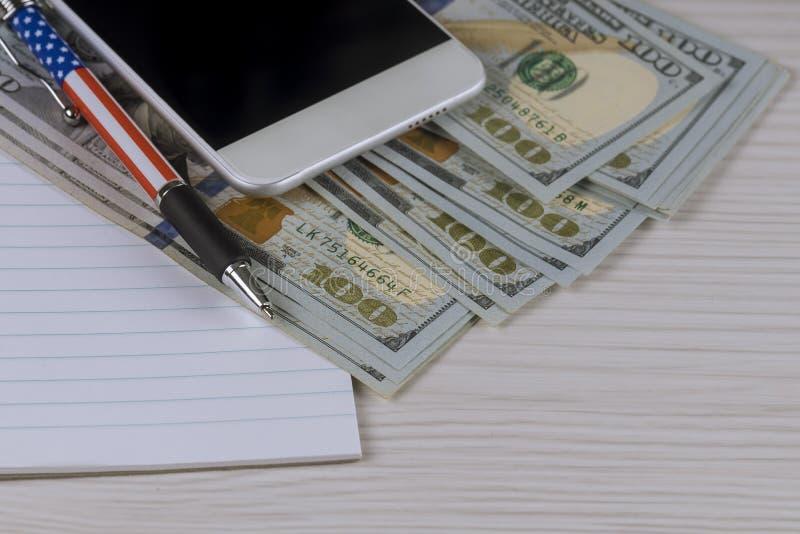 Smartphone, un cuaderno y pluma en cientos billetes de d?lar fotos de archivo libres de regalías