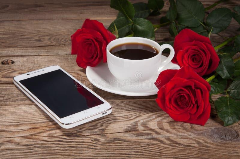 Smartphone, una taza y rosas en la tabla vieja imagen de archivo
