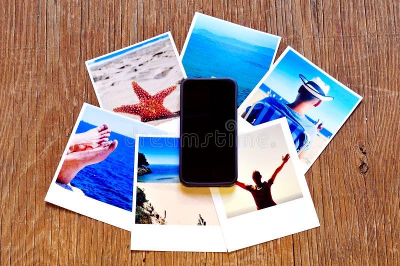 Smartphone und einige Fotos auf einer Holzoberfläche stockfoto