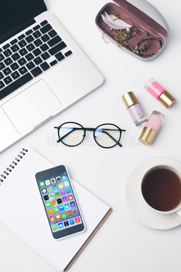 top view of laptop and smartphone with unlocked iphone homescreen on girly workplace stock image
