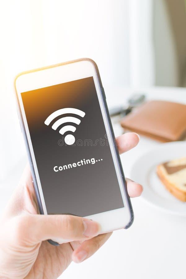 Smartphone van de handholding en verbindend WiFi-netwerk royalty-vrije stock afbeeldingen