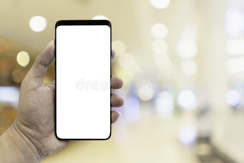 Smartphone van de handholding met onduidelijk beeldbinnenland in winkelcomplex stock foto