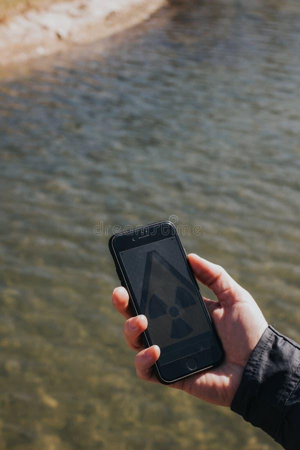 Smartphone van de handholding met stralingspictogram royalty-vrije stock afbeelding