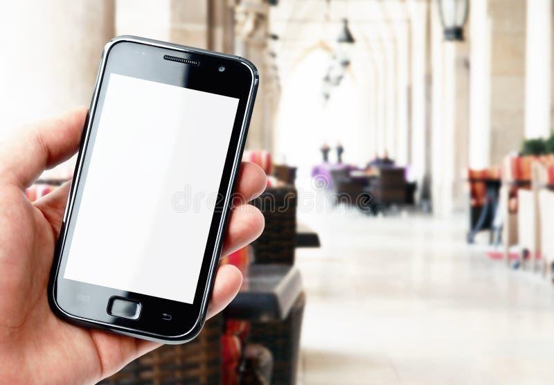 Smartphone van de handholding in stadskoffie stock fotografie