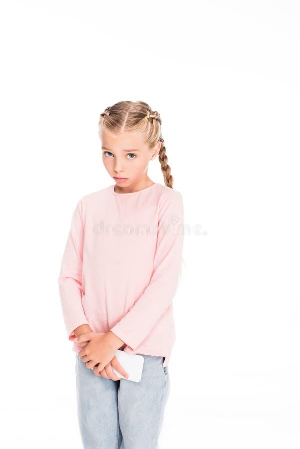 Smartphone van de jong kindholding met schuldige blik op haar gezicht, stock fotografie