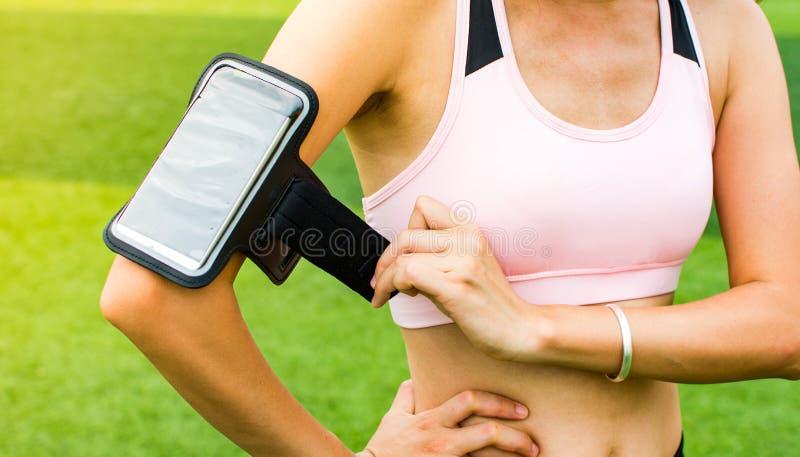 Smartphone van de meisjesvestiging aan de activiteit van de spoorjogging royalty-vrije stock fotografie