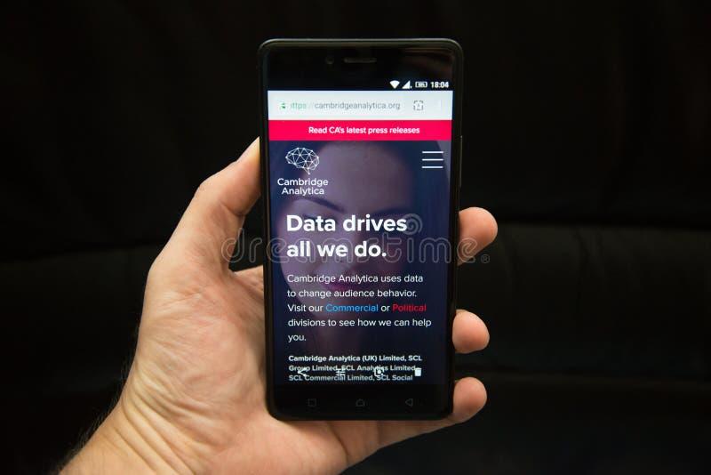Smartphone van de mensenholding met Cambridge Analytica stock foto