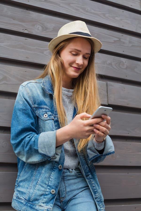 Smartphone van de tienervrouw buiten houten muur royalty-vrije stock foto's